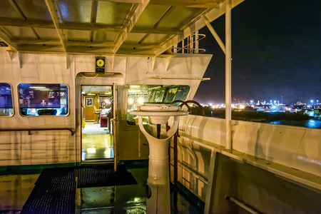 navigational: Wing bridge deck of a freighter ship with navigational equipment at rainy night