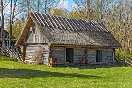 Old wooden barn with thatched roof and two doors on Hiiumaa island old farm, Estonia