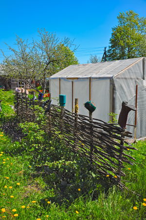 yard stick: Traditional lath fence around a farmers house with clay pots and other trash items on top of stakes