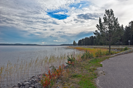 back country: Back country road along the coast of forest lake. Stock Photo