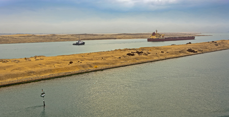 convoy: Loaded Bulk carrier passing through Suez Canal with ships convoy at early morning. Stock Photo
