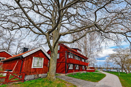 ochre: Red ochre painted colour wooden houses on waterfront of lake Malar in Sigtuna, Sweden. Founded in 980 Sigtuna is the oldest city in Sweden and a popular tourist destination. Editorial