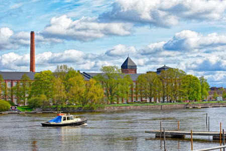 North shore of the Kokemaenjoki River with the classical industrial architecture houses of the former cotton factory in Pori, Finland