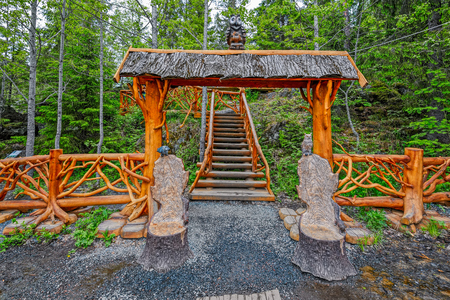 fense: SORTAVALA, RUSSIA - MAY 28, 2016: Ornate wooden gate with cariving bird statues and fense at the entrance to the observation deck of waterfall and river Tokhmajoki (Ruskeala) in the Republic of Karelia, Russia