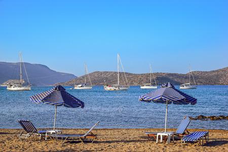 beachfront: Beach scene with lounge chairs, umbrellas and yacht in Mirabello Bay, Crete. Stock Photo