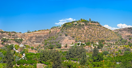 Panoramic top view from mountain to Cyprus landscape with gardens, mountain villages and country road between hills