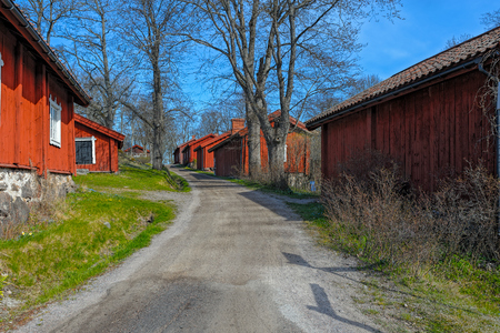 Traditional red ochre painted colour wooden houses at Fagervik Ironworks works street, Finland. Most of the surviving huts date to the beginning of the 19th century.