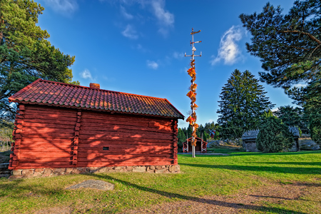 Farmhouses and traditional midsummer pole at Jan Karlsgarden open air museum at autumn sunset. Aland Islands, Finland Editorial