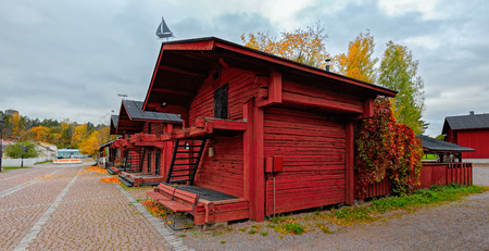 host: Red ochre historic wooden salt warehouses have been turned into restaurants or spaces that host art exhibitions and shops an historic district Laivasilta in small coastall town Loviisa, Finland Stock Photo