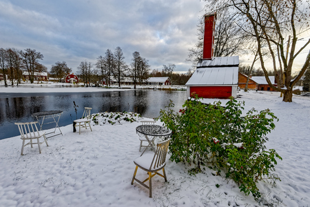 Chairs and tables to rest covered with snow and standing in deep snow on shore pond in front of the red ochre painted colour wooden houses of former Stromfors Iron Works. Finland