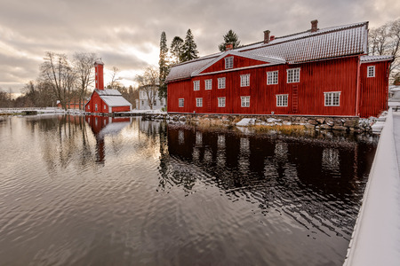 ochre: Traditional red ochre painted colour wooden houses at former Stromfors Iron Works, Finland covered first snow Stock Photo