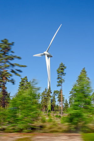 Wind turbine for renewable electric energy production along the road with clear sky background, Finland