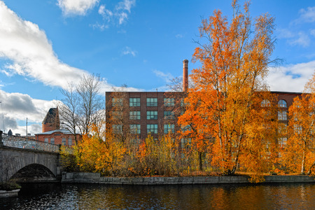 famous industries: Fall colors and old factory building of red brick on  embankments channel of rapids Tammerkoski. Tampere, Finland Stock Photo