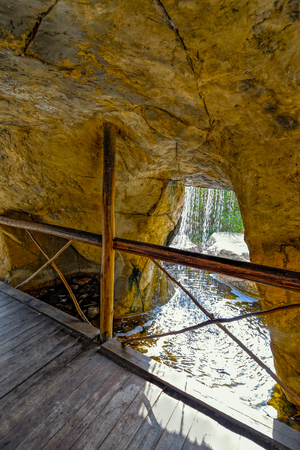 man made: Cave with wooden bridge under man made waterfall