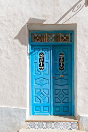 Decorated arabic style blue door in white wall with shadow of lantern, Tunisia, Africa