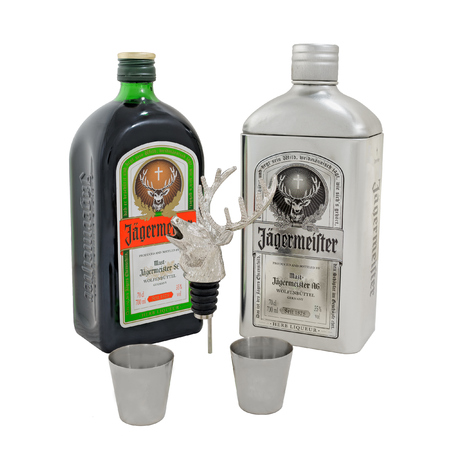 Jagermeister Gift Pack with bottle, silver tin storage stash box, stag deer head pourer and two stainless steel shot glasses on white background. Jagermeister is a German alcohol drink made with 56 different herbs and spices.