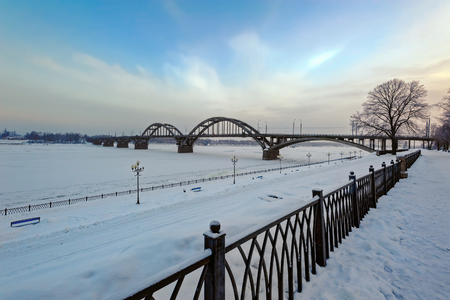 Automobile road bridge over frozen Volga River in the city of Rybinsk at cold winter sunrise. Russia