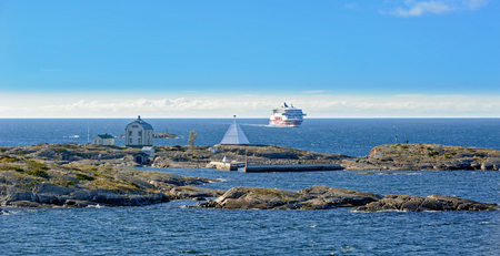 Aland, Finland - October 07, 2016: Ferry of the shipping company Viking Line on Baltic Sea on the way from Sweden to Finland in the archipelago of Aland Kobba Klintar island with Old Pilot Station Editöryel