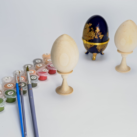Close-up view to painting by number on wood billet of Easter egg with stand on white background