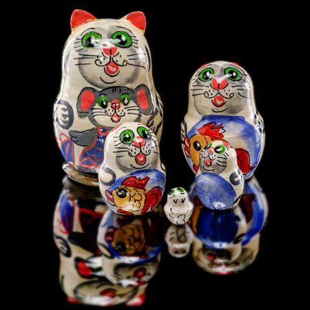 Set of Russian nesting dolls (babushkas or matryoshkas) in shapes of cat family on black mirror