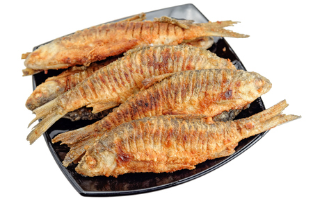 fish tail: Fried freshwater fish roach on a black plate