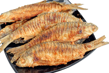 freshwater: Fried freshwater fish roach on a black plate