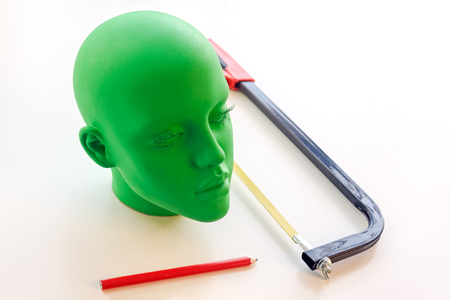 Green female mannequin head, pencil and saw on table Stock Photo