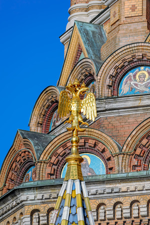 Double-headed Russian imperial eagle sits at the top of the steeple of the Church of the Savior on Spilled Blood in Saint-Petersburg, Russia in the winter.