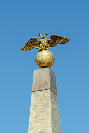 Double-headed Russian imperial eagle sits at the top of the Tsarina stone obelisk on Market Square in Helsinki, Finland.