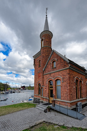 Small storytelling castle in red brick and slate roofs, with a tower and a tourell as well as a corner tower - Skridskopaviljongen on the island of Kastellholmen. Stockholm, Sweden. Stock Photo