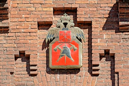 Russian fire department coat of arms on red brick wall of firetower