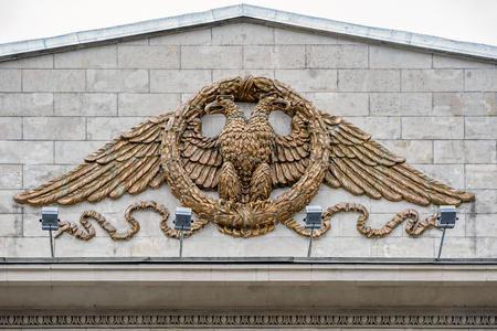 Newly restored Russian two-headed eagle sitting in a wreath (pottery, bronze) on facade of the building of the department store DLT - House of Leningrad Trade.