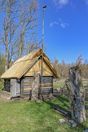 Old wooden sauna log cabin with thatched roof in traditional estonian style on countryside old farm. Hiiumaa island, Estonia