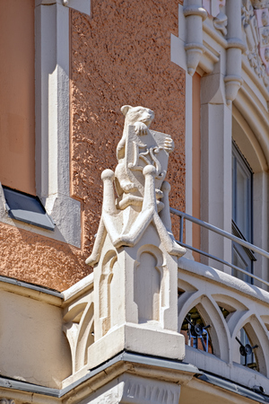 Detail of Art Nouveau style building  with richly decorated facade with grotesque stone figure sitting bear holds the coat of arms. Helsinki, Finland