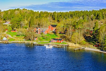 화창한 아침에 아름 다운 휴가 주택과 보트와 발트 해에서 스톡홀름 열도의 바위 해안 스톡 콘텐츠