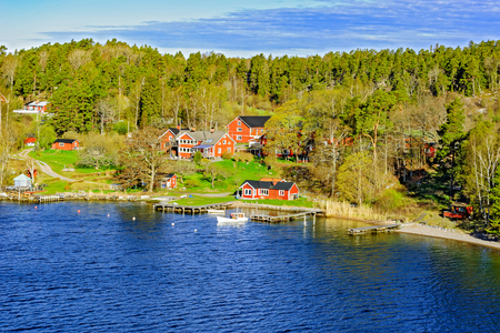 Rocky coast of Stockholm archipelago in Baltic sea with picturesque vacation houses and boats at sunny morning
