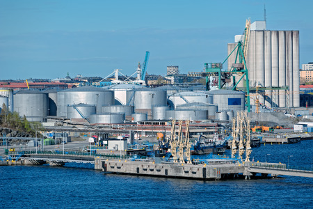warehouse: Oil tanks of fuel storage area and other silos at Stockholm industrial sea port district. Sweden Stock Photo