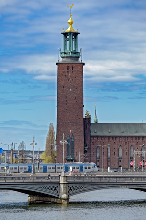 spire: View to Stockholm City Hall over Centralbron (The Central Bridge) with local train. Sweden
