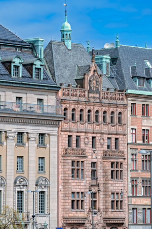 Ornate decorated brownish red sandstone facade with bas-relief, stculpture, clock and golden plated weathervane on spire in Stockholm, Sweden.