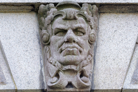 stucco facade: Allegorical mascaron (sculpture picturing a face doing a grimace) by sculptor Gustaf Fredrik Norling and designed by Aron Johansson on the wall of Parliament House.