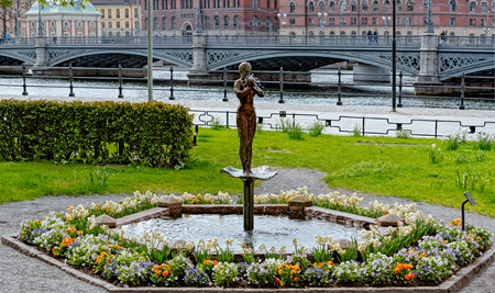 Woman statue fountain in Rosenbadsparken with the Riddarholm Church and the Vasabron bridge on background. Stockholm, Sweden