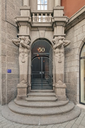 telamon: Stone carving in art deco style depicting telamons over gates of Kungsgatan building number 30 Northern Kings tower in Stockholm.