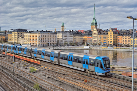 Cityscape of Gamla Stan city district in central Stockholm with blue passenger trains passing through bridge. Editorial