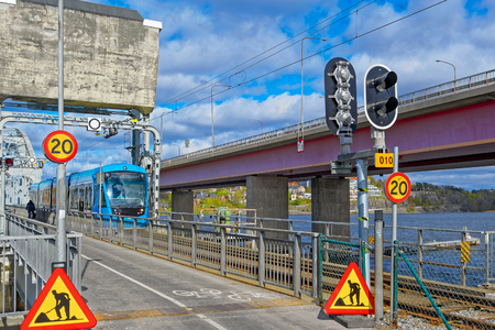 Blue articulated CAF tram of class A36 in service for SL crossing the Old Lidingo bridge on the line Lidingobanan near the final destination Ropsten in Stockholm.