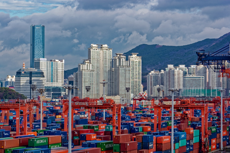 BUSAN, SOUTH KOREA - Dec 22, 2016: Sunrise panorama container cargo terminal of Port of Busan, Koreas busiest and the 10th-busiest in the world, in front of residential multistorey buildings. Editorial