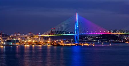BUSAN, SOUTH KOREA - Jan 21, 2017: Sunset view to illuminated suspension Busan North Port Bridge with multicolored nighttime LED Light Show. Busan, South Korea. Editöryel