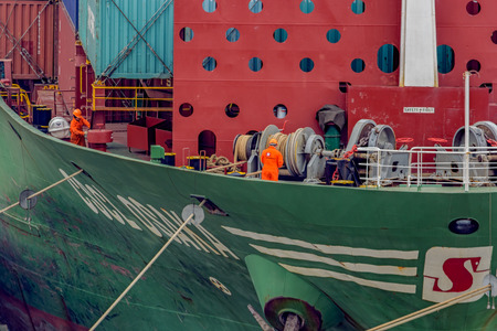 SHANGHAI, CHINA - Mar 17, 2017: Unidentified sailors adjusts mooring winches and ropes as bow of cargo ship comes in to dock