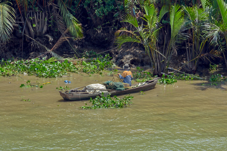 HO CHI MINH CITY (SAIGON), VIETNAM - Feb 27, 2017: Vietnamese fishermen is searching for snakes and shells in the green muddy water of NHA Be river at low tide. Editorial
