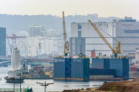 precast: BUSAN, SOUTH KOREA - Mar 22, 2017: Giant precast concrete section of the new bridge is loaded onto the cargo floating dry dock WOONGJIN FD-15000 for delivery to the construction site by waterway.