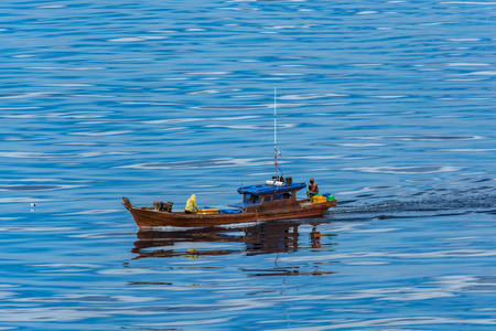 Local wooden fishing boat in Strait of Singapore.